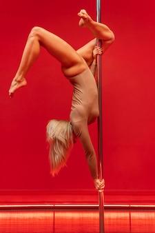 Выступление молодой женщины на полюсном танце
