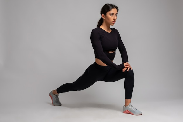 Young woman performing forward lunges on grey wall