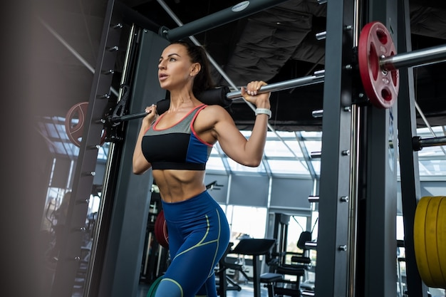 Young woman performing lunges on smith machine at gym