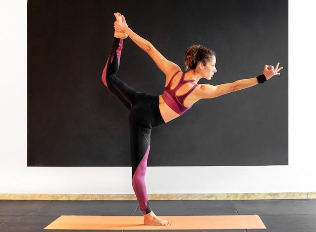 Young woman performing a natarajasana yoga pose