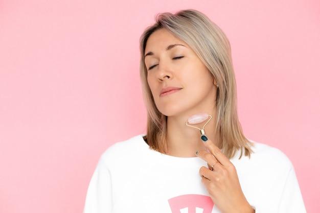 Молодая женщина выполняет самомассаж шеи роликом гуаша. концепция личной гигиены, антивозрастной уход, ролик гуаша. фото крупным планом