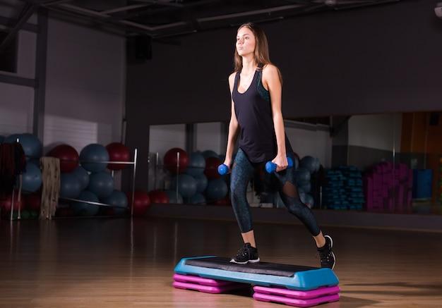 若い女性がジムでダンベルを使って有酸素運動を行う