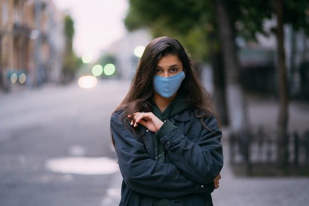 若い女性、空の通りで防護医療滅菌マスクの人
