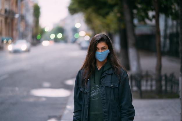 若い女性、空の通りに立っている防護医療滅菌マスクの人