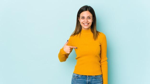 自信を持って自信を持ってシャツのコピースペースを手で指している若い女性人