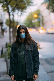Young woman, person in protective medical sterile mask at empty street