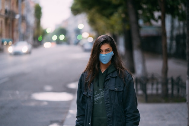 Young woman, person in protective medical sterile mask standing at empty street,