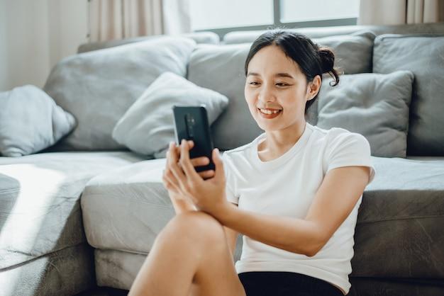 Молодая женщина, использующая мобильный телефон для связи с киберпространством, держит смартфон и отправляет текстовое сообщение, женщины довольны умными технологиями, образ жизни девушки для бизнеса в интернете