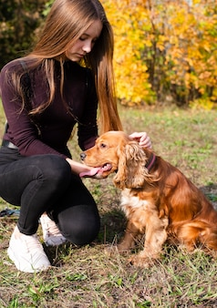 Young woman petting cocker spaniel
