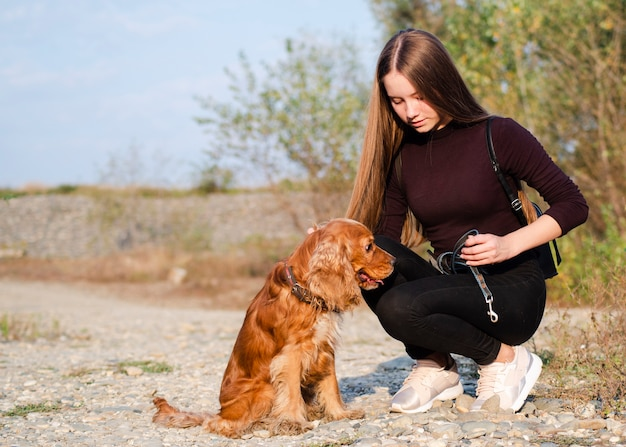 Young woman petting a cocker spaniel