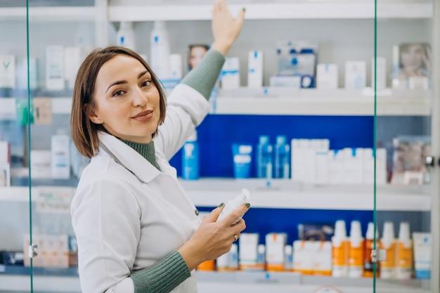Молодая женщина-фармацевт в аптеке