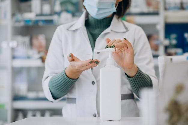 Farmacista della giovane donna che disinfetta le mani con disinfettante