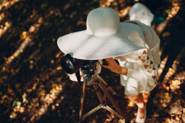 Фотограф молодой женщины в белом платье и шляпе с камерой в осеннем парке.
