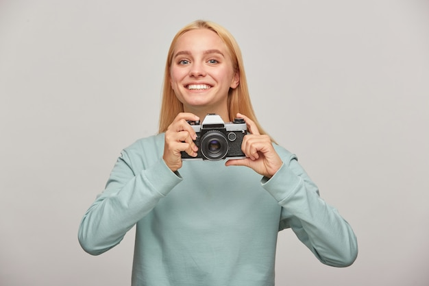 Young woman photographer looks happily smiling, holding a retro vintage photo camera in hands