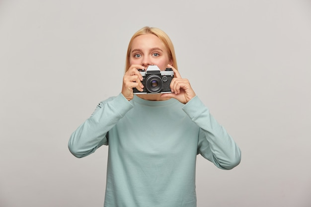 Young woman photographer looks out from behind the lens, holding a retro vintage photo camera