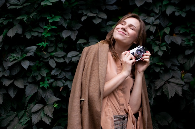 Young woman photographer stands with a film camera near a wall of leaves in the forest, a woman photographs in nature