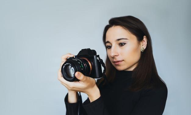 若い女性写真家は、photostudioで現代のデジタルカメラで写真を撮ります。白い壁の壁にカメラを持つ少女。