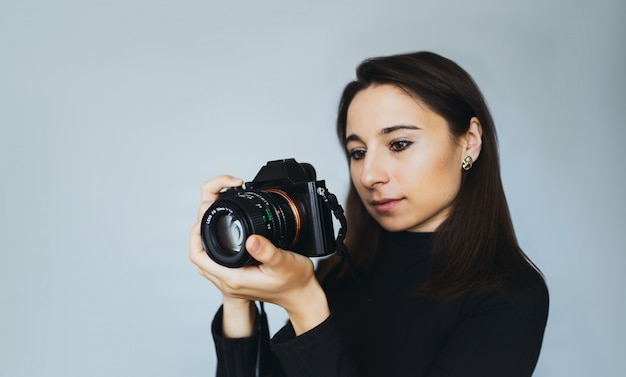 Young woman photographer takes photographs with modern digital camera in a photostudio. girl with  a camera  on a wall of a white wall.