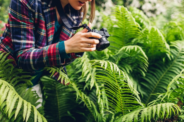 Young woman photographer taking photos on digital camera in summer park. happy freelancer taking pictures of fern. relaxing enjoying hobby