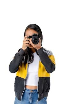 카메라를 손에 들고 흰색 배경으로 사진을 찍는 젊은 여성 사진사.