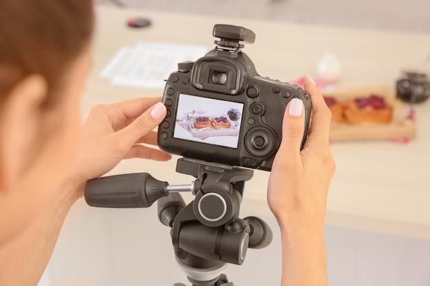 Молодая женщина фотографирует еду в фотостудии