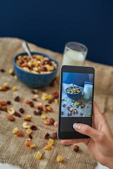 Молодая женщина фотографирует ее завтрак. девушка ест хлопья для завтрака с орехами, тыквенными семечками, овсом и в миске с молоком. девушка держит смартфон. здоровый перекус или завтрак по утрам.