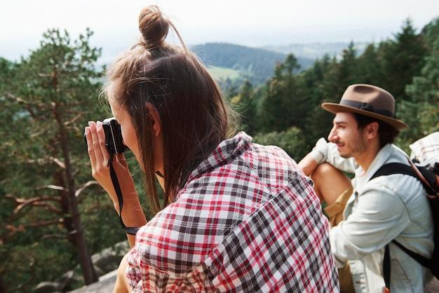 山の風景を撮影する若い女性