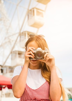 Young woman photographing with camera at amusement park