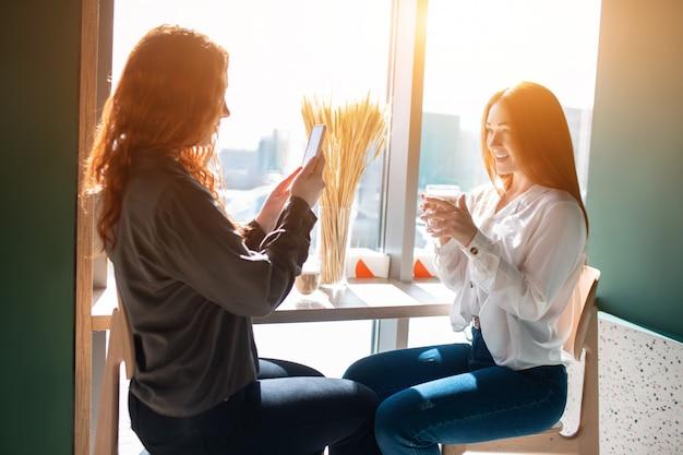 Молодая женщина фотографирует своего друга. женская модель фотографирует с чашкой кофе в руке.