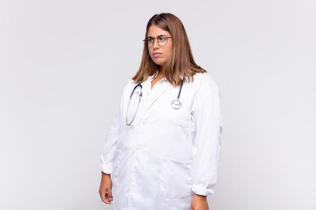 젊은 여성 의사가 슬프거나 화를 내거나 화를 내고 부정적인 태도로 옆을 바라보며 의견이 일치하지 않습니다.