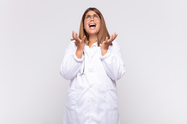 Young woman physician looking desperate and frustrated, stressed, unhappy and annoyed, shouting and screaming