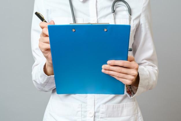 患者に治療を処方する聴診器で若い女性医師。クリップボードにレシピを書くペンを持つ女性医師。グレーに分離