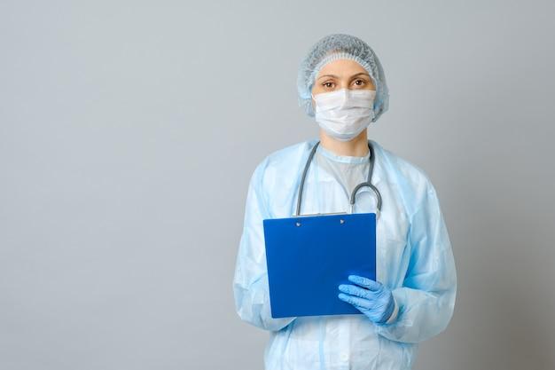 聴診器で患者に治療を処方する若い女性医師。クリップボードにレシピを書くペンを持つ女性医師。グレーに分離
