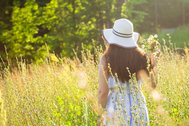 여름 저녁 뒷모습에서 초원에서 꽃을 따는 젊은 여성