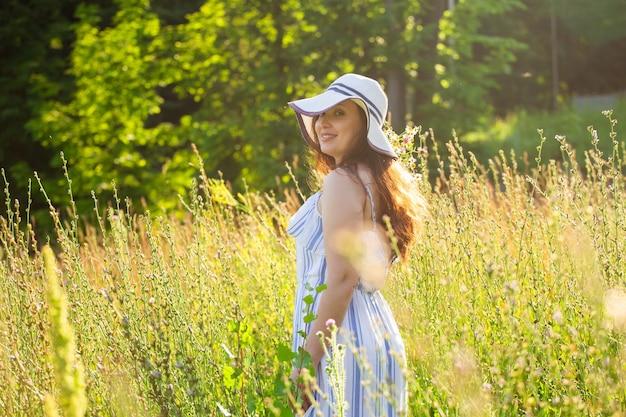 여름 저녁에 초원에서 꽃을 따는 젊은 여자