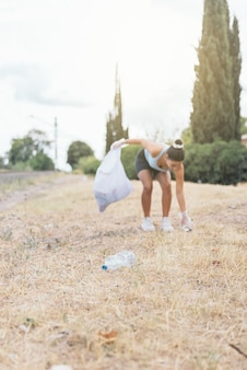 Молодая женщина собирает мусор с земли для переработки