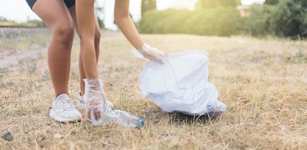 재활용을 위해 땅에서 쓰레기를 줍는 젊은 여성
