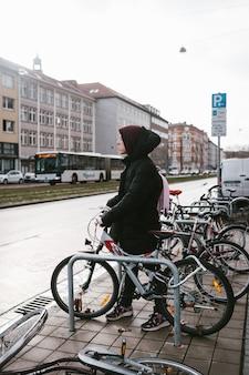 La giovane donna prende la sua bici dal parcheggio