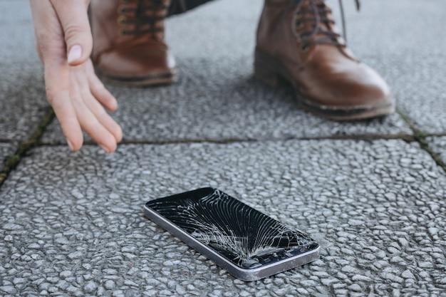 Молодая женщина поднимает свой сломанный смартфон с треснувшим экраном после падения.