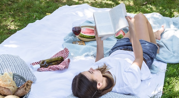 A young woman at a picnic reading a book