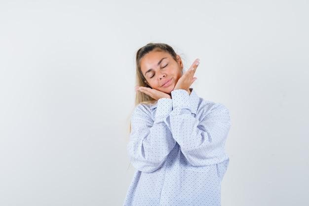 Молодая женщина подпирает лицо руками, держит глаза закрытыми в белой рубашке и выглядит мило