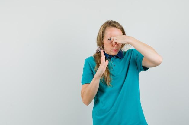 Tシャツの嫌なにおいで鼻をつまんで嫌そうな若い女性。