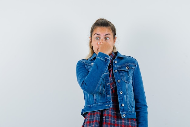 Young woman pinching nose, feeling bad smell in shirt, jacket front view.