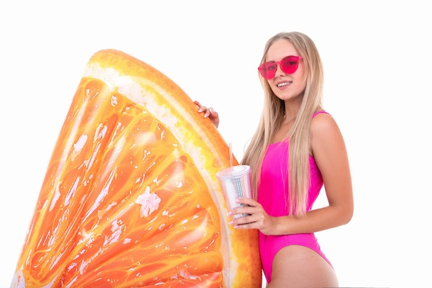 A young woman in a pink bathing suit drinks lemonade and holds an air mattress