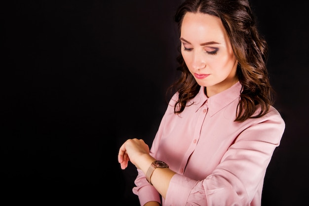 Young woman in pink blouse on black background looks at clock