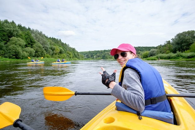 Young woman in pink cap rowing in kayak over the river, having fun