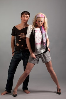 Young woman in pink clothing embracing young man in black from back over gey background in photo studio. beauty and fashion lifestyle concept