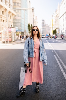 Young woman in an pink dress, denim jacket, boots and eye cat sunglasses standing at the famous view of gran via main broadway road in the downtown of madrid, spain .