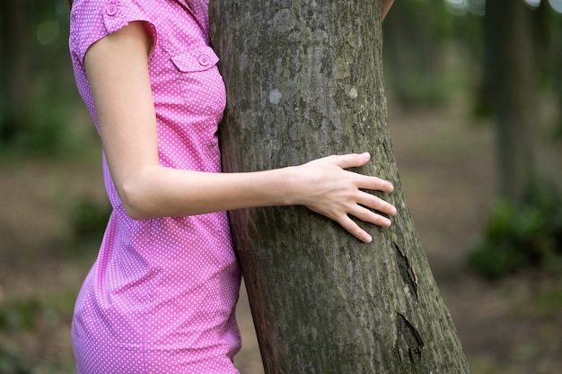 Young woman in pink dress leaning to tree trunk hugging it with her hands in summer forest