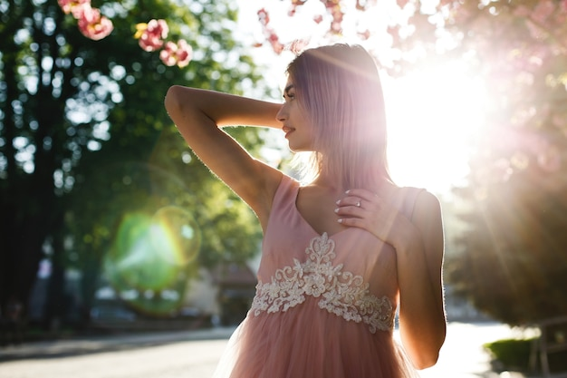 Young woman in pink dress poses before a sakura tree full of pink flowers and illuminated